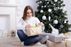 打开一个圣诞节礼物的少妇在一圣诞节早晨 免版税图库摄影