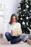 打开一个圣诞节礼物的少妇在一圣诞节早晨 免版税库存图片