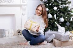打开一个圣诞节礼物的少妇在一圣诞节早晨 库存照片