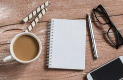 打开一个干净的笔记薄、笔、玻璃、电话、咖啡和饼干 办公室咖啡休息 库存图片