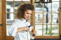 打开一个瓶啤酒的女性厨师在厨房 免版税库存照片