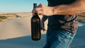 打开一个瓶啤酒的年轻人室外在沙漠沙丘 图库摄影