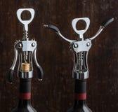 打开一个瓶在木背景的酒的翼拔塞螺旋 免版税库存照片