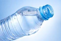 打开一个瓶在蓝色背景的水 免版税库存照片
