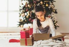 打开一个礼物的逗人喜爱的女孩在一圣诞节早晨 免版税库存图片
