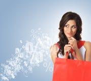 打开一个红色购物袋的美丽的妇女 免版税库存照片
