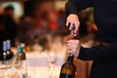 打开一个红葡萄酒瓶的妇女 免版税库存图片