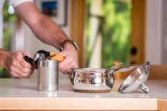 打开一个罐头与开罐头用具的辣椒 免版税库存图片