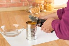 打开一个罐头与开罐头用具的玉米的妇女 免版税库存照片