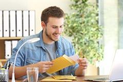 打开一个被填塞的信封的企业家 免版税库存照片