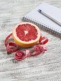 打开一卷空白的笔记薄、葡萄柚和测量的磁带在一张轻的木桌上 健康营养,饮食的概念 免版税库存照片