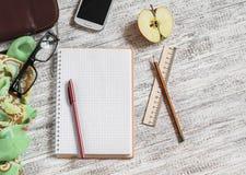 打开一条空白的笔记薄、笔、玻璃、电话、提包和围巾 免版税库存图片