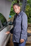 打开一辆汽车的门在车库的年轻技工 免版税库存图片
