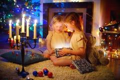打开一件不可思议的圣诞节礼物的可爱的小女孩 免版税图库摄影