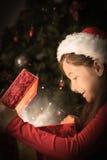 打开一件不可思议的圣诞节礼物的小女孩的综合图象 免版税库存图片