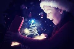打开一件不可思议的圣诞节礼物的小女孩的综合图象 免版税图库摄影