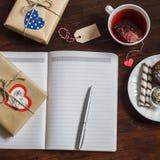 打开一件干净的空白的笔记薄、情人节自创礼物、一杯在木棕色桌上的茶和甜点 库存照片