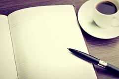 打开一份空白的白色笔记本、笔和咖啡在书桌上 免版税库存图片