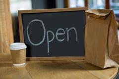 打开与一次性咖啡杯和纸袋的牌在桌上 免版税库存图片