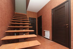打开与上升至在明亮的墙壁和黑暗的门背景的里面走廊房间特写镜头的石步的楼梯  库存照片