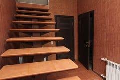打开与上升至在明亮的墙壁和黑暗的门背景的里面走廊房间特写镜头的石步的楼梯  免版税库存图片