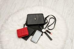 打开与下降的事、笔记本、手机、手表、红色钱包和唇膏的黑袋子 在背景,顶视图的白色毛皮 免版税库存图片
