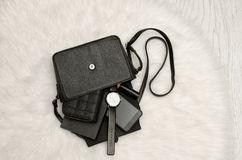 打开与下降的事、笔记本、手机、手表、钱包和唇膏的黑袋子 在背景,顶视图的白色毛皮 库存图片
