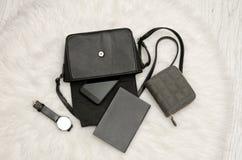 打开与下降的事、笔记本、手机、手表和灰色钱包的黑袋子 在背景,顶视图的白色毛皮 库存照片