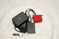 打开与下降的事、笔记本、手机、手表和红色钱包的黑袋子 在背景,顶视图的白色毛皮 时尚co 免版税库存图片
