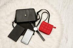 打开与下降的事、笔记本、手机、手表和红色钱包的黑袋子 在背景,顶视图的白色毛皮 免版税库存照片