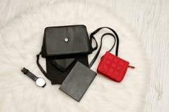 打开与下降的事、笔记本、手机、手表和红色钱包的黑袋子 在背景,顶视图的白色毛皮 库存照片