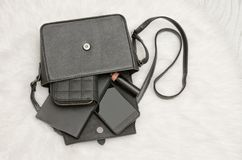 打开与下降的事的黑袋子,笔记本,手机,钱包 在背景,顶视图的白色毛皮 秀丽蓝色聪慧的概念表面方式构成妇女 免版税库存照片