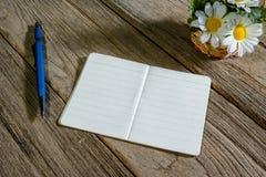 打开与传动器型的铅笔的笔记本在木背景 图库摄影