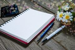 打开与传动器型的铅笔的笔记本在木背景 库存照片