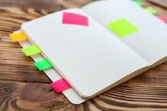 打开与办公用品的笔记薄 开放笔记薄在有标志、铅笔、笔和贴纸的一个木桌面上说谎 免版税库存图片