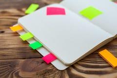 打开与办公用品的笔记薄 开放笔记薄在有标志、铅笔、笔和贴纸的一个木桌面上说谎 库存照片