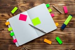 打开与办公用品的笔记薄 开放笔记薄在有标志、铅笔、笔和贴纸的一个木桌面上说谎 库存图片