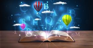 打开与发光的幻想抽象云彩和气球的书 库存图片