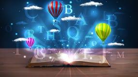 打开与发光的幻想抽象云彩和气球的书 免版税库存图片