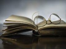 打开与古色古香的放大镜的书 图库摄影