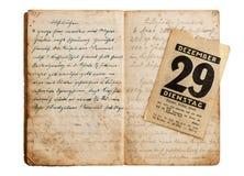 打开与古色古香的日历页的老菜谱 免版税库存照片