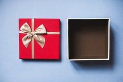 打开与弓的红色礼物在蓝色背景顶视图 库存照片