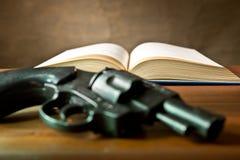 打开与手枪的书 免版税库存照片