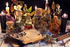 打开与拷贝空间的书、草本和莓果、黑蜡烛和不可思议的对象在巫婆桌上 免版税库存照片