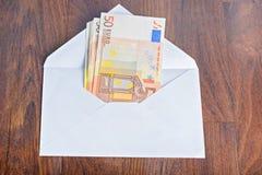 打开与欧洲钞票的信封在桌上 免版税库存图片