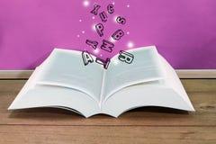 打开与漂浮对此的信件的书与一个桃红色委员会 免版税库存图片