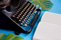 打开与用打字机和叶子装饰的白纸页的书在明亮的蓝色背景-与拷贝空间 免版税库存照片