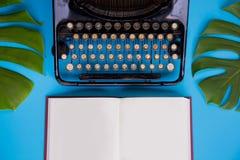 打开与用打字机和叶子装饰的白纸页的书在明亮的蓝色背景 免版税库存图片
