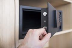 打开与电子锁关闭的安全门 在家保留金钱和首饰 供以人员` s手和保险柜在公寓 图库摄影