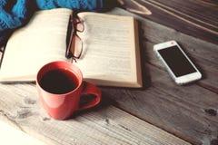 打开与电话的书、玻璃和咖啡或者茶顶视图在桌上 库存图片